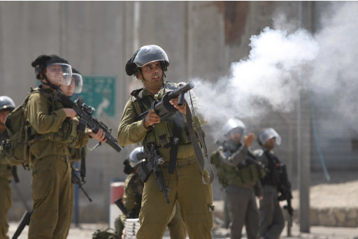 Israeli soldiers fire tear gas canisters at Palestinian protesters, not seen, during clashes at the Qalandia checkpoint between the West Bank city of Ramallah and Jerusalem, Wednesday, Sept. 21, 2011. Palestinians clashed with Israeli security forces in Qalandia Wednesday, as thousands of flag-waving Palestinians rallied in towns across the West Bank to show support for their president's bid to win U.N. recognition of a Palestinian state. (AP Photo/Majdi Mohammed)