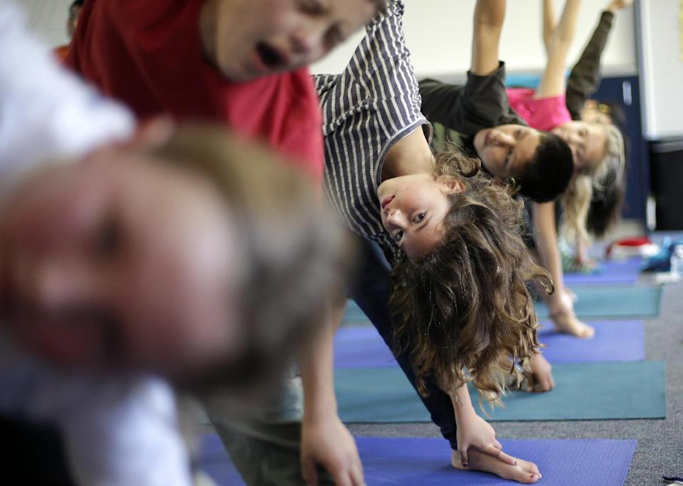 FILE - In this Dec. 11, 2012 file photo, students hold their position during a yoga class at Capri Elementary School in Encinitas, Calif. A San Diego County judge has ruled that the Encinitas Union School District was not teaching religion by offering yoga classes. (AP Photo/Gregory Bull, File)
