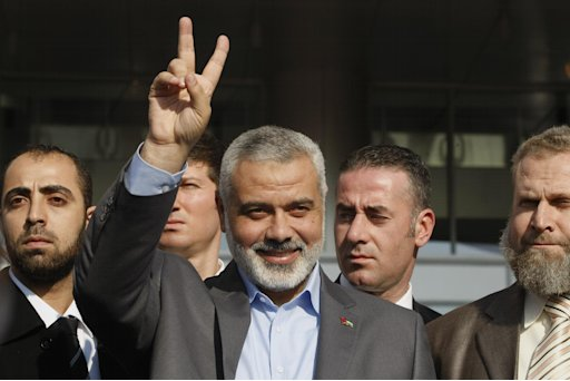 The Gaza Strip's Hamas Premier Ismail Haniyeh is surrounded by security guards as he makes a victory sign after a meeting with a Turkish leader in Ankara, Turkey, Tuesday, Jan. 3, 2012. Haniyeh visited the Mavi Marmara, the ship that was the target of a deadly raid by Israeli troops seeking to prevent an aid flotilla reaching the Palestinian territory, in Istanbul on Monday. Haniyeh's visit was a show of solidarity with the Islamic aid group IHH, which had planned to send the Mavi Marmara vessel with another Gaza flotilla last year but then dropped the plan.(AP Photo/Burhan Ozbilici)