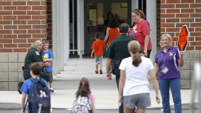 A Gilchrist County Sheriff's deputy greets students as they arrive for class at Bell Elementary School on Friday, Sept. 19, 2014 in Bell, Fla. On Thursday, 51-year-old Don Spirit killed six of his grandchildren, including an infant, his adult daughter and himself in a rampage. Four of the children attended Bell Elementary. (AP Photo/The Gainesville Sun, Matt Stamey)