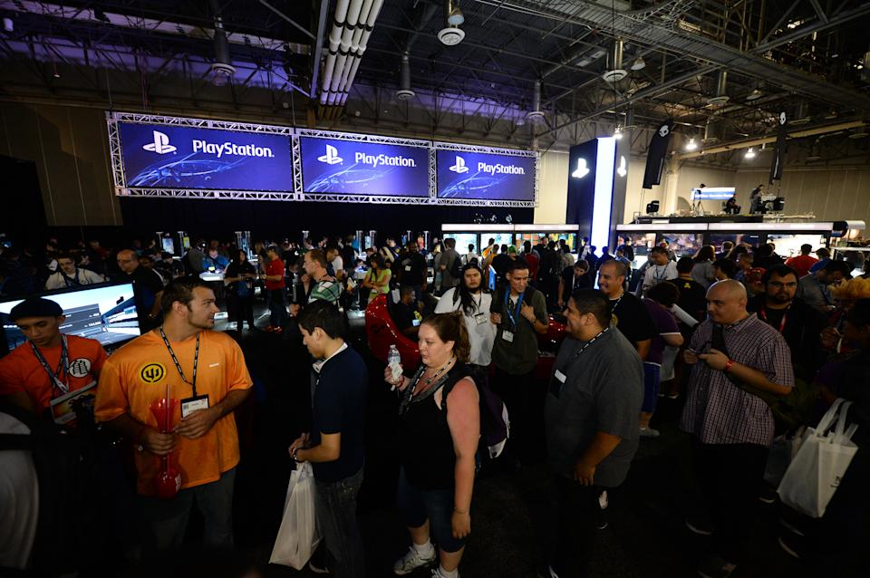Attendees walk near the Sony Playstation booth at the GameStop Expo in Las Vegas on Wednesday, Aug. 28, 2013. (Photo by Al Powers/Invision/AP)