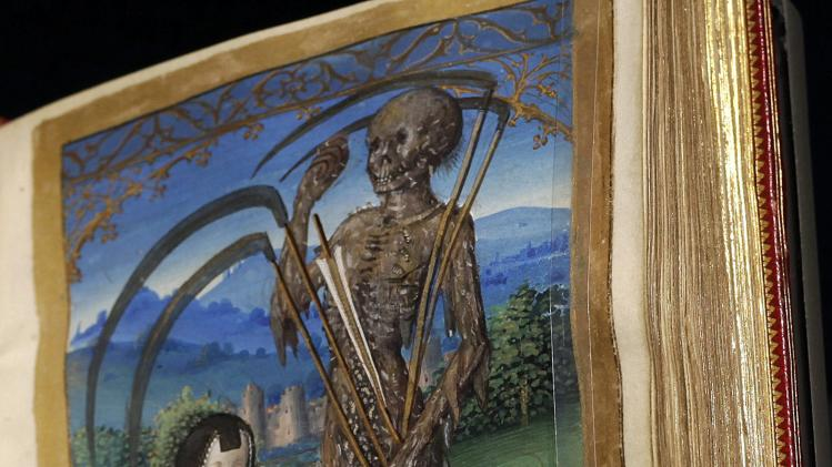 "In this photo taken Tuesday, May 29, 2012, A prayer book titled, ""Denise Poncher before a Vision of Death,"" Paris, about 1500, depicts the owner Denise Poncher kneeling with her prayer book before Death, a terrifying skeleton covered with rotting flesh and holding numerous sickles.  is displayed at the ""Heaven, Hell and Dying Well: Images of Death in the Middle Ages"" exhibit at The Getty Museum in Los Angeles. The exhibition goes back to the 15th century to unearth some of the mankind's earliest, most colorful images of life's final chapter. (AP Photo/Damian Dovarganes)"