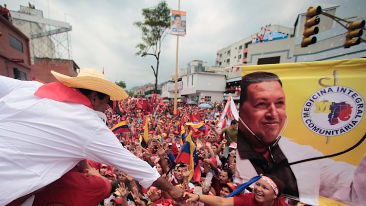 In this photo released by Miraflores Press Office, Venezuela's acting President Nicolas Maduro, left,  reaches out to greet supporters during a campaign rally in Trujillo, Venezuela, Wednesday, April 10, 2013. Maduro, the hand-picked successor of the late President Hugo Chavez, is running for president against opposition candidate Henrique Capriles. The presidential election is set for Sunday, April 14. (AP Photo/Miraflores Press Office)