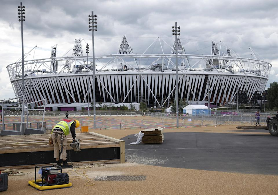 A construction worker builds a stand outside the Olympic Stadium as preparations continue for the 2012 Summer Olympics, Sunday, July 15, 2012, in London. (AP Photo/Jae Hong)