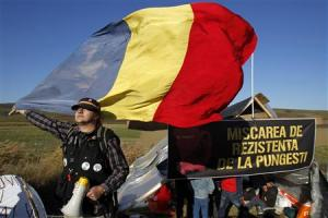 A man holds Romania's national flag in front of a tent installed on the empty lot where U.S. oil major Chevron plans to search for shale gas in Pungesti