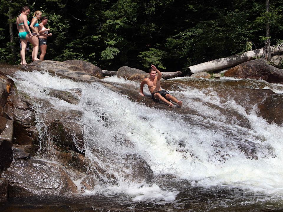 People keep cool while swimming in the water at the Lower Falls of the Swift River, Tuesday, July 16, 2013 in Albany, N.H. A weeklong heat wave continues to bear down on much of the region. (AP Photo/Jim Cole)