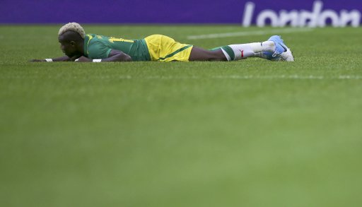 Senegal's Pape Souare lies on the pitch during their men's preliminary first round Group A soccer match against Uruguay at the London 2012 Olympic Games in the Wembley Stadium in London