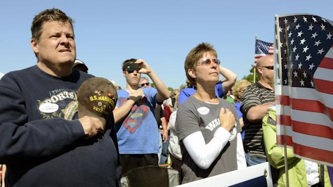 People put their hands over their hearts as the National Anthem is played before a rally held by the Racine Tea Party PAC in Gorney Park in Caledonia, Wis. near Racine on Saturday, June 2, 2012. The rally was held in opposition to the Tuesday, June 5, 2012 recall election in which Democratic opponents are running against incumbent Gov. Scott Walker, Lt. Gov. Rebecca Kleefisch, and State Sen. Van Wanggaard of Racine. At least 2,000 people attended the event. (AP Photo/Mark Hertzberg)