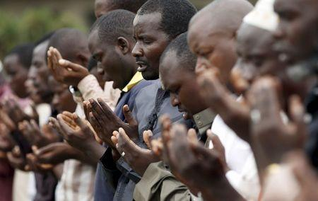 Men pray in front of a house of Zedi Feruzi,the head of opposition party UPD, during his funeral in Bujumbura