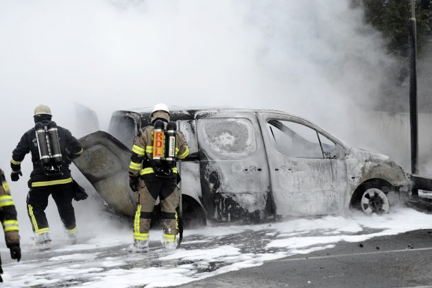 Firemen inspect a burnt car in the suburb of Rinkeby after youths rioted in several different suburbs around Stockholm
