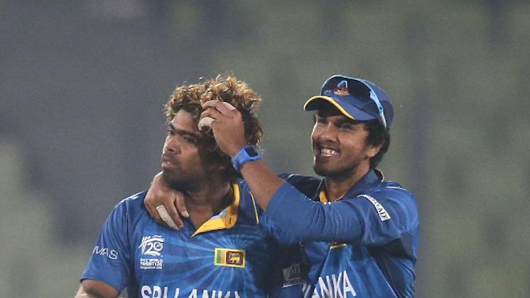 Sri Lanka's bowler Lasith Malinga, left, celebrates with captain Dinesh Chandimal after the dismissal of India's batsman Virat Kohli during their ICC Twenty20 Cricket World Cup warm up match in Dhaka, Bangladesh, Monday March 17, 2014. (AP Photo/Aijaz Rahi)