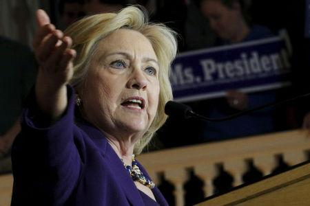 U.S. Democratic presidential candidate Hillary Clinton speaks in front of an audience member holding a sign in Boston