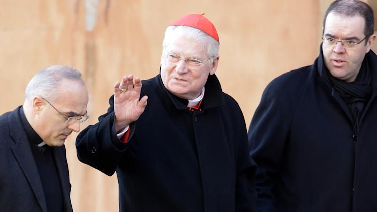 Italian Cardinal Angelo Scola, center, waves to reporters as he arrives with two unidentified assistants, for a meeting, at the Vatican, Monday, March 4, 2013. Cardinals from around the world have gathered inside the Vatican for their first round of meetings before the conclave to elect the next pope, amid scandals inside and out of the Vatican and the continued reverberations of Benedict XVI's decision to retire. (AP Photo/Andrew Medichini)