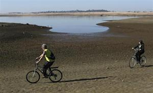 Visitors ride bicycles near the receding waters at Folsom Lake, which is 17 percent of its capacity, in Folsom