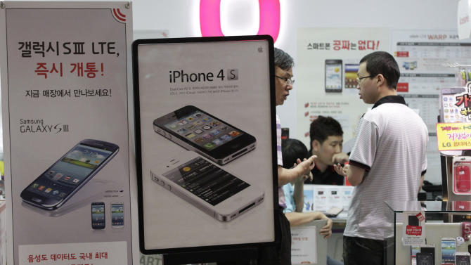 Banners advertising Samsung Electronics' Galaxy S III, left, and Apple's iPhone 4S are displayed at a mobile phone shop in Seoul, South Korea, Friday, Aug. 24, 2012. The Seoul Central District Court ruled Friday that technology rivals Apple Inc. and Samsung Electronics Co. both infringed on each other's patents, and ordered a partial ban of their products in South Korea. Each side was also ordered to pay limited damages. The court ordered Apple to remove the iPhone 3GS, iPhone 4, iPad 1 and iPad 2 from store shelves in South Korea, ruling that the products infringed on two of Samsung's telecommunications patents. (AP Photo/Ahn Young-joon)