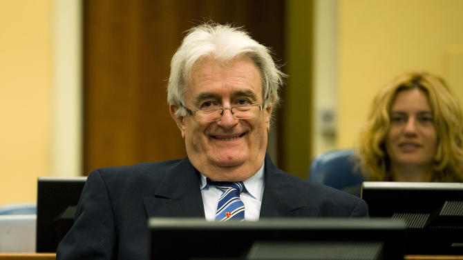 Suspected war criminal and the former leader of Serbs in Bosnia, Radovan Karadzic, left, smiles when taking his seat on the defense bench in the court room to start his defense at the U.N. war crimes tribunal in the Hague in The Hague, Netherlands, Tuesday Oct. 16, 2012. (AP Photo/Robin van Lonkhuijsen, pool)
