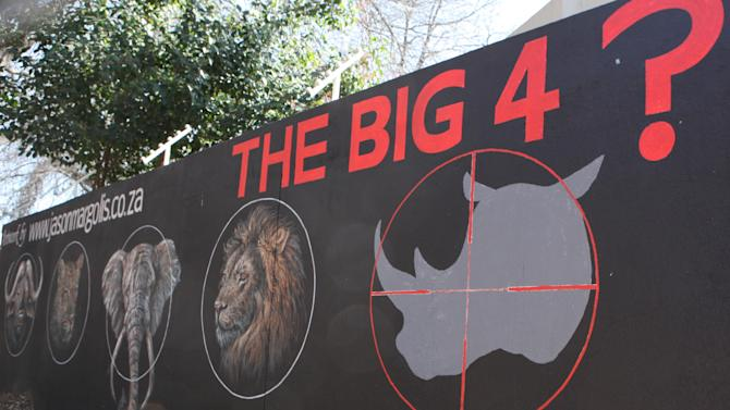 """A mural painted on a suburban wall in Johannesburg, South Africa calls for the halt to rhino poaching, Monday, July 21, 2014. Officials at Kruger park, South Africa's flagship wildlife reserve, are considering a plan to move some rhinos out of the park in an attempt to protect them from poachers. A spokesman said that no decision has been made on the plan adding that the idea would be to """"spread the risk"""" to other reserves because the Kruger park is heavily targeted by poachers, many of whom cross from neighboring Mozambique. (AP Photo/Denis Farrell)"""