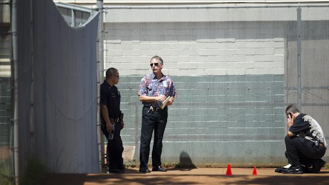 Police detectives investigate a campus shooting at Highlands Intermediate School May 23, 2011 in Pearl City, Hawaii.  Honolulu police say a handgun brought to school by a Hawaii middle school student was fired on campus, leaving one student with minor injuries.  (AP Photo/Marco Garcia)