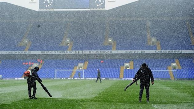Groundstaff clear snow off the pitch at White Hart Lane (PA Photos)