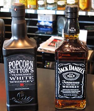 Bottles of Popcorn Sutton's Tennessee White Whiskey and Jack Daniel's Tennessee whiskey sit side by side at a Louisville, Ky., liquor store. The owner of the Jack Daniel's trademark has filed a federal lawsuit claiming the shape of the Popcorn Sutton bottle amounts to a trademark infringement because it so closely resembles the Jack Daniel's bottle. AP Photo/Bruce Schreiner.