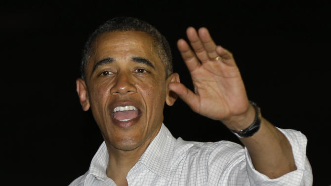 President Barack Obama waves to base peronnel before boarding Air Force One to return to Washington, at Honolulu Joint Base Pearl Harbor-Hickam in Honolulu, after spending Christmas with his family in Hawaii, Wednesday, Dec. 26, 2012. (AP Photo/Gerald Herbert)