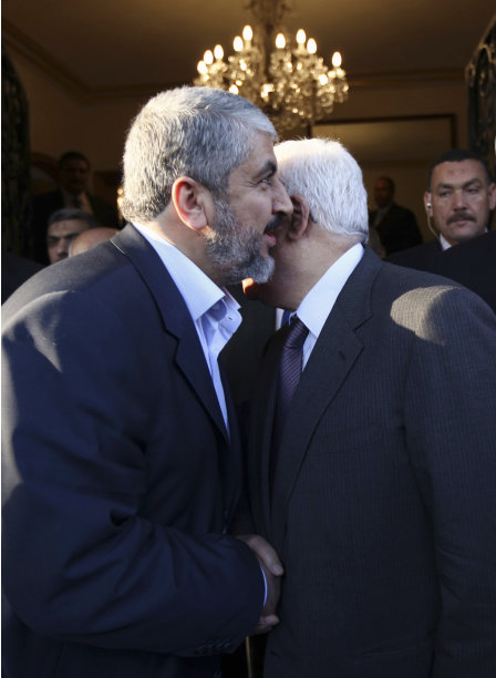 In this photo provided by the office of Khaled Meshaal, Palestinian Hamas leader Khaled Mashaal, left, and Palestinian President Mahmoud Abbas greet each other during their meeting in Cairo, Egypt, Thursday, Nov. 24, 2011. The long-estranged leaders of the two rival Palestinian political movements said Thursday they significantly narrowed differences and opened a new page in relations in reconciliation talks in Cairo. (AP Photo/Office of Khaled Meshaal) EDITORIAL USE ONLY, NO SALES