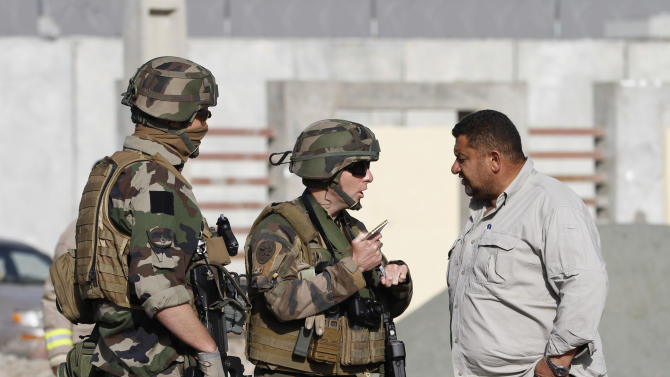 French soldiers talk to an Afghan security official at the scene of a suicide bombing, Tuesday, Sept. 18, 2012 in Kabul, Afghanistan. A suicide bomber rammed a car packed with explosives into a mini-bus carrying foreign aviation workers to the airport in the Afghan capital early Tuesday, killing at least nine people in an attack a militant group said was revenge for an anti-Islam film that ridicules the Prophet Muhammad. (AP Photo/Ahmad Jamshid)