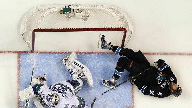 San Jose Sharks center Joe Thornton, right, collides with Vancouver Canucks goalie Cory Schneider during the second period of Game 3 of their first-round NHL hockey Stanley Cup playoff series in San Jose, Calif., Sunday, May 5, 2013. (AP Photo/Marcio Jose Sanchez)