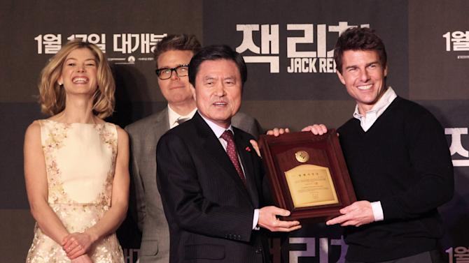 """U.S. actor Tom Cruise, right, receives a certificate of Busan citizenship from Busan City mayor Hut Nam-shik, second from right, before a premiere of his new movie """"Jack Reacher"""" as British actress Rosamund Pike, left, and director Christopher McQuarrie look on at the Busan Cinema Center in Busan, South Korea, Thursday, Jan. 10, 2013. (AP Photo/Ahn Young-joon)"""