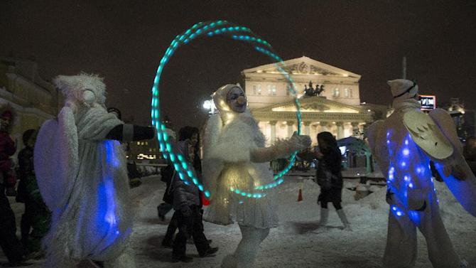 People dressed in illuminated angel costumes parade to mark the Christmas Day, with the Bolshoi Theater in background, in central Moscow, Russia, on Thursday, Dec. 25, 2014. (AP Photo/Pavel Golovkin)