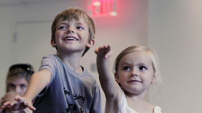 """In this Sept. 5, 2012, photo, from left, Aidan Lain, 7, and Zoe Shyba, 3, play """"Kinect Sesame Street TV"""" at the Sesame Street Workshop  in New York. """"Kinect Sesame Street TV"""",  launching Tuesday,  Sept. 18, 2012, uses Kinect, a motion and voice-sensing controller created by Microsoft, to give Elmo, Big Bird and the rest of the Sesame Street crew a chance to have a real two-way conversation with their pint-sized audience. The effort represents the next step in the evolution of television, adding an interactive element to what's still largely a passive, lean-back experience. (AP Photo/Mark Lennihan)"""