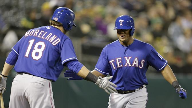 Texas Rangers' Adrian Beltre, right, is congratulated by Mitch Moreland (18) after hitting a home run off Oakland Athletics' Chris Resop in the tenth inning of a baseball game Tuesday, May 14, 2013, in Oakland, Calif. (AP Photo/Ben Margot)
