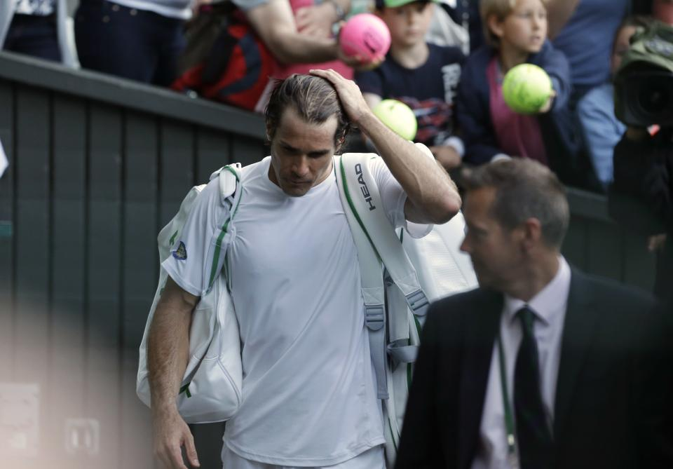 Tommy Haas of Germany reacts as he walks off the court after losing to Novak Djokovic of Serbia during a Men's singles match at the All England Lawn Tennis Championships in Wimbledon, London, Monday, July 1, 2013. (AP Photo/Anja Niedringhaus)