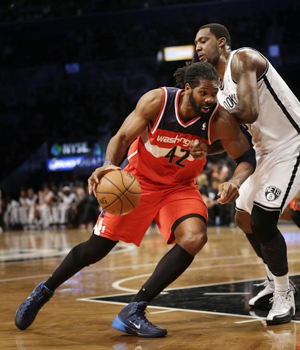 Washington Wizards' Nene Hilario, left, tries to push past Brooklyn Nets' Andray Blatche during the first half of an NBA basketball game Wednesday, Dec. 18, 2013, in New York