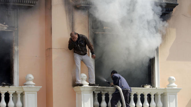 Policemen try to extinguish fire at a police club set by protesters following a court verdict in Cairo, Egypt, Saturday, March 9, 2013. Fans of Cairo's Al-Ahly club have stormed Egypt's soccer federation headquarters, set it ablaze after a court acquitted seven of nine police officials on trial for their alleged part in deadly stadium melee. A fire also broke out Saturday in a nearby police club, but it was not immediately known whether Al-Ahly fans started the blaze there too. (AP Photo/Amr Nabil)