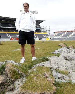 England rugby team coach Martin Johnson looks at damage to the pitch inside the AMI Stadium in Christchurch, New Zealand, Wednesday, Sept., 7, 2011. Christchurch was to have been the base for the England team for the upcoming Rugby World Cup. However due to the earthquake of Feb. 22, 2011, and the damage done to infrastructure, hotels and stadium, their base and all their matches have been moved away from Christchurch. (AP Photo/Alastair Grant)