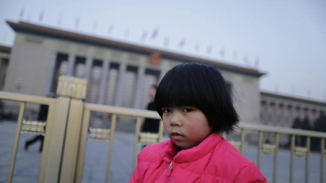 A girl stands in front of the Great Hall of the People in Beijing