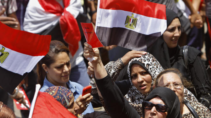 """Egyptian protesters shout slogans and wave national flags and one waves a red card with Arabic reads, """"down with the brotherhood rule"""" during a demonstration against Egypt's Islamist President Mohammed Morsi in Tahrir Square in Cairo, Monday, July 1, 2013. Elsewhere in Cairo, protesters stormed and ransacked the headquarters of President Mohammed Morsi's Muslim Brotherhood group early Monday, in an attack that could spark more violence as demonstrators gear up for a second day of mass rallies aimed at forcing the Islamist leader from power.(AP Photo/ Amr Nabil)"""
