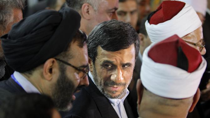 Iran's President Mahmoud Ahmadinejad, center, attends a press conference with Egyptian Sunni clerics at Al-Azhar headquarters in Cairo, Egypt, Tuesday, Feb. 5, 2013. Egypt's most prominent Muslim cleric, the sheik of Al-Azhar, has warned Iranian President Mahmoud Ahmadinejad against interfering in Arab Gulf countries or trying to spread Shiite influence. Ahmadinejad, on a landmark visit to Egypt on Tuesday, received an uneasy reception from Ahmed el-Tayeb at Al-Azhar, the Sunni Muslim world's foremost Islamic institution.(AP Photo/Amr Nabil)