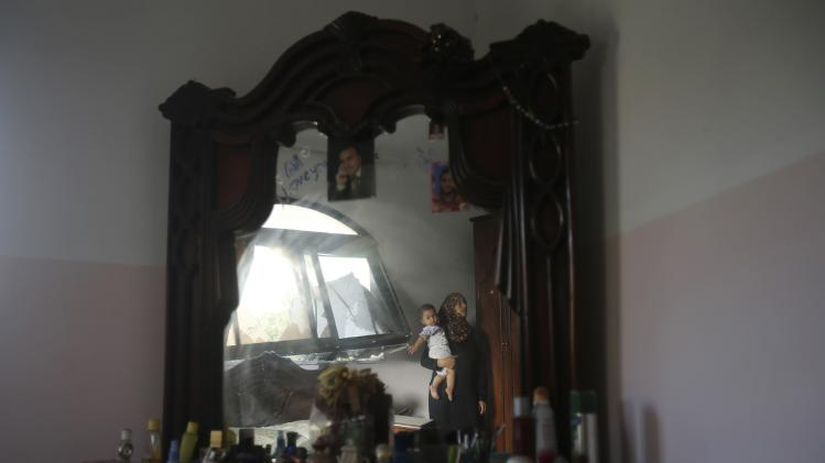 A Palestinian woman carrying her child is reflected in a mirror as she looks at her bedroom, which witnesses said was damaged in an Israeli air strike, in Khan Younis