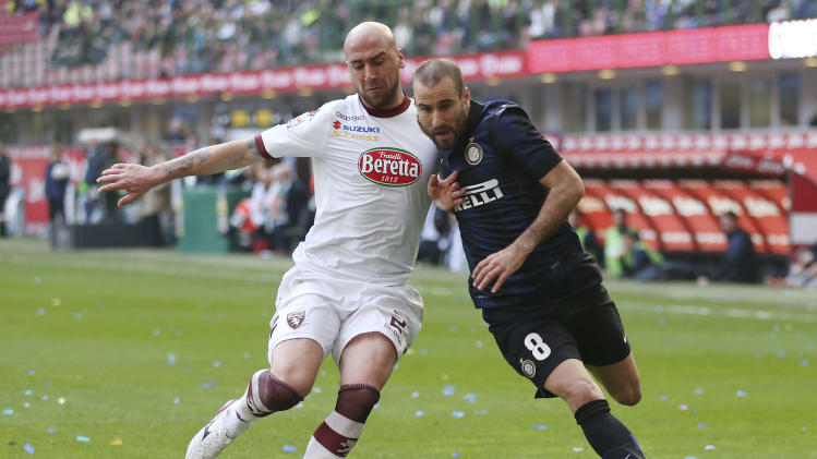 Inter Milan forward Rodrigo Palacio, right, of Argentina, challenges for the ball with Torino defender Guillermo Rodriguez, of Uruguay, during the Serie A soccer match between Inter Milan and Torino at the San Siro stadium in Milan, Italy, Sunday, March 9, 2014. (AP Photo/Antonio Calanni)