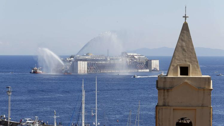 Tugboats spays water in farewell to the cruise liner Costa Concordia during the refloat operation maneuvers at Giglio Island