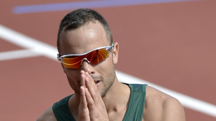 FILE - This is a Saturday, Aug. 4, 2012 file photo of South Africa's Oscar Pistorius  as he reacts after finishing first in a men's 400-meter heat during the athletics in the Olympic Stadium at the 2012 Summer Olympics, London  Paralympic superstar Oscar Pistorius was charged Thursday Feb. 14. 2013 with the murder of his girlfriend who was shot inside his home in South Africa, a stunning development in the life of a national hero known as the Blade Runner for his high-tech artificial legs. (AP Photo/Martin Meissner, File)