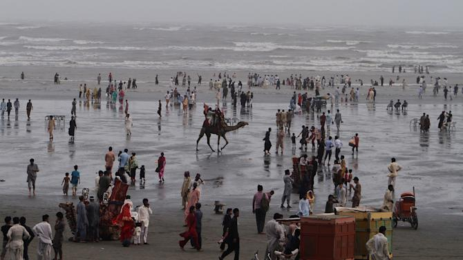 People visit Clinfton beach, during a hot summer's day in Karachi, Pakistan, Sunday, July 5, 2015. Many cities in Pakistan are facing heat wave conditions with temperatures reaching up to 47 degrees Celsius (116.6 Fahrenheit) in some places. (AP Photo/Fareed Khan)