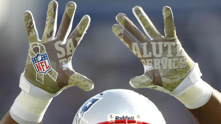 "New England Patriots linebacker Jermaine Cunningham holds up his gloves, which sport the words ""Salute to Service"" in honor of Veteran's Day, during the first quarter of an NFL football game against the Buffalo Bills at Gillette Stadium in Foxborough, Mass., Sunday, Nov. 11, 2012. (AP Photo/Stephan Savoia)"