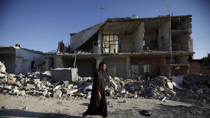 A Syrian man walks by a house destroyed in a Syrian government bombing last week that killed more than 40 people, in Azaz, on the outskirts of Aleppo, Syria, Friday, Aug. 24, 2012. (AP Photo/Muhammed Muheisen)
