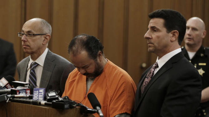 Ariel Castro, center, stands before a judge with his defense attorney's, Jaye Schlachet, left, and Craig Weintraub during his arraignment Wednesday, June 12, 2013, in Cleveland. A grand jury charged Castro with two counts of aggravated murder related to one act, saying he purposely caused the unlawful termination of one of the women's pregnancies. He also was indicted on 139 counts of rape, 177 counts of kidnapping, seven counts of gross sexual imposition, three counts of felonious assault and one count of possession of criminal tools. Castro pleaded not guilty. (AP Photo/Tony Dejak)