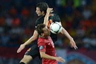 Dutch forward Robin van Persie (back) and Portuguese defender Joao Pereira jump for a header during the Euro 2012 football championships match Portugal vs. Netherlands at the Metalist stadium in Kharkiv. Portugal beat the Netherlands 2-1 on Sunday to set up a Euro 2012 quarter-final with the Czech Republic and condemn the Dutch to a first group-stage European Championship exit since 1980