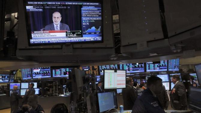 Traders work at their posts as a news conference of U.S. Federal Reserve Board Chairman Ben Bernanke is braodcast on the floor of the New York Stock Exchange