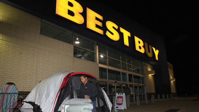 Stefan Rood, 20, folds blankets as he cleans out his tent outside a Best Buy Thursday, Nov. 22, 2012, in Mayfield Heights, Ohio. while waiting for the store to open at 12 a.m. on Friday. Rood, who has been camped out since Wednesday night, is looking to buy a new cell phone. (AP Photo/Tony Dejak)
